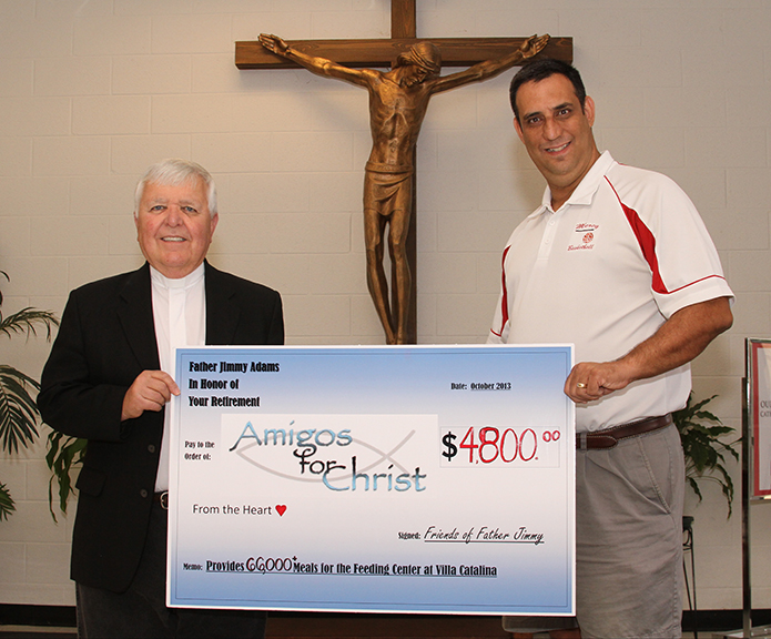 Tony Caruso, right, holds the retirement gift he presented to Father Jimmy Adams, left, from friends and former parishioners that took the form of a check representing donations to Amigos for Christ. The two worked together at Our Lady of Mercy High School, Fayetteville, where Caruso is a teacher and coach, and Father Adams was the chaplain for the past six years.