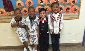 (L-r) St. Peter Claver Regional School pre-K students Fabian and Favian Murry and Charlie Moncayo and kindergartener Samuel Lian take pride in their heritages from Kenya, Mexico and Burma, respectively. The Decatur school hosted its first multicultural celebration Oct. 21 with Mass and a sampling of international cuisine.