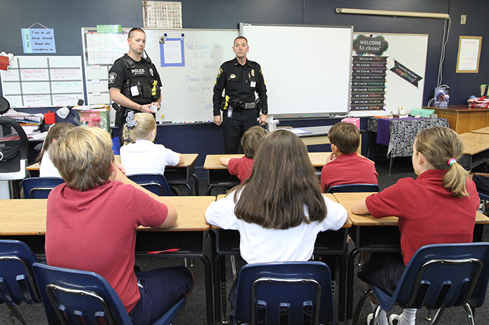 Sgt. Jake Kissel, right, of the Brookhaven Police Department makes his first visit of the school year, Sept. 14, to Kathryn Berg's fifth grade class at Our Lady of the Assumption School. Sgt. Kissel, who was adopted by the entire fifth grade, which includes two other classrooms, brought police K9 handler Officer David Fikes, left, as a special guest. Photo By Michael Alexander