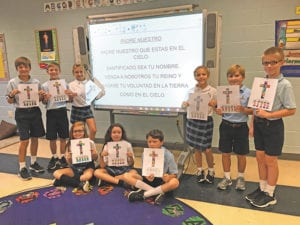 St. Mary's School, Rome, fifth-grade students surround a projection of the Our Father in Spanish, which was prayed by the school on Friday, Sept. 9. Images of the cross were also colored by younger grades.